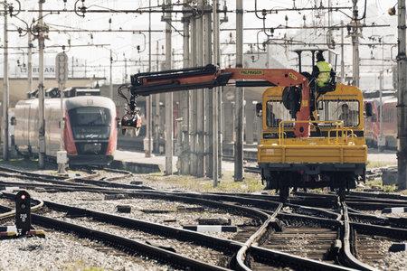 Ljubljana, Slovenia - March 17, 2020: Workers with tie crane doing the railroad maintenance at train station in Ljubljana, Slovenia Redakční