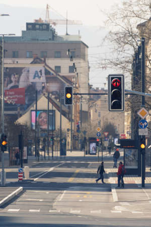 Ljubljana, Slovenia - March 17, 2020: Red and yellow traffic lights in downtown Ljubljana, Slovenia on nearly empty streets with few people during the Coronavirus Covid-19 outbreak Redakční