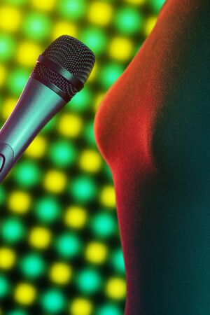 Closeup of woman singer standing next to vocal microphone illuminated by bright disco lights in background. Music, singing, disco, karaoke and sound reproduction.