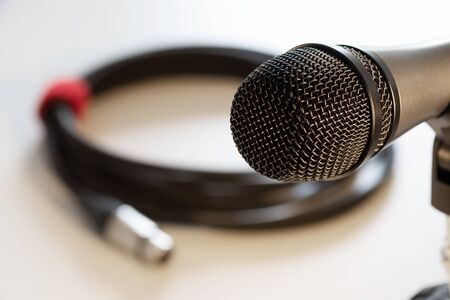 Closeup of vocal microphone head with black grille and cable with xlr connector in background isolated on white. Music, audio, hi-fi, karaoke and sound reproduction.