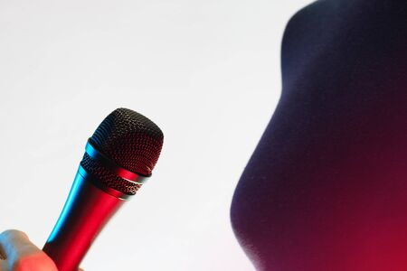 Closeup of woman holding a blue and red illuminated vocal microphone on white background. Music, singing, disco, karaoke and sound reproduction.