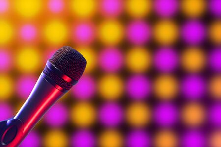 Closeup of Vocal microphone on pink, purple and yellow disco background lighting. Music, singing, disco, karaoke and sound reproduction.