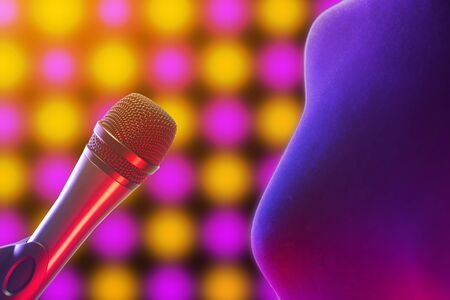 Closeup of woman standing next to vocal microphone illuminated by disco lights in background. Music, singing, disco, karaoke and sound reproduction.