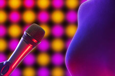 Closeup of vocal microphone and woman torso next to it illuminated by disco lights in background. Music, singing, disco, karaoke and sound reproduction. Reklamní fotografie