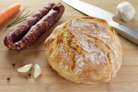 Freshly baked homemade wheat bread on wooden cutting board with dry sausage, garlic and spices. Gourmet, healthy food, cuisine, pastry and diet concepts Reklamní fotografie
