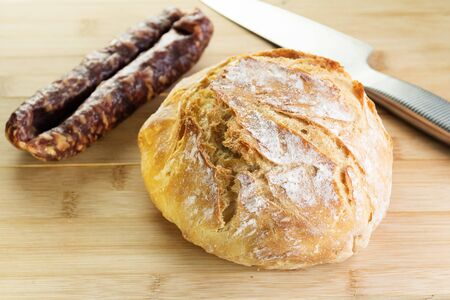 Homemade bread, dry smoked sausage and knife on wooden cutting board. Gourmet, healthy food, local cuisine, pastry and diet concepts