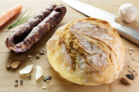 Homemade wheat bread on wooden cutting board with dry sausage, garlic, seeds and spices. Gourmet, healthy food, cuisine, pastry and diet concepts Reklamní fotografie