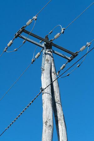 Old wooden three-phase electric utility pole with high voltage electricity cables and a clear blue sky in background. Electricity, power distribution and technology concepts