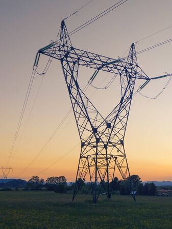 High voltage transmission power line tower with orange sunset background. Electricity, power distribution and technology concepts