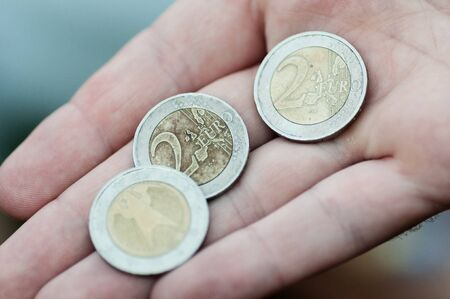 Closeup of three weathered 2 Euro coins in male hand