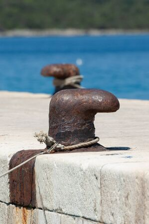 Old and rusty mooring bollard on concrete pier with blue sea in background. Sailing, vacation, travel, tourism and maritime activities concepts