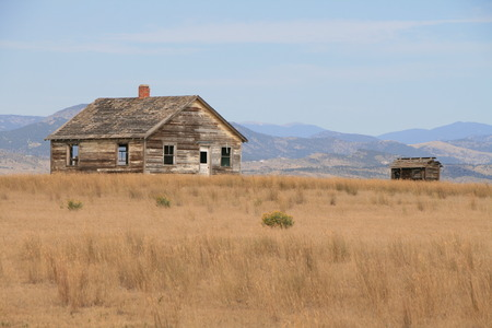 homestead: Old abandoned homestead with mountain backdrop in the high plains