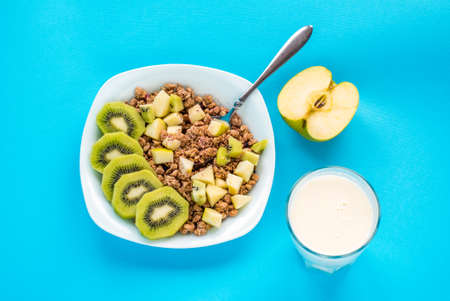 Muesli with kiwi and apple with milk on  blue Standard-Bild - 154759299