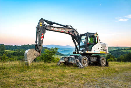 Volovets, Ukraine - 08/27/2020: HIDROMEK 140w excavators on a background of mountains and forests. Standard-Bild - 154232825