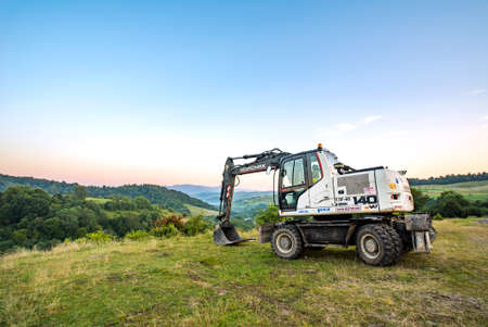 Volovets, Ukraine - 08/27/2020: HIDROMEK 140w excavators on a background of mountains and forests.
