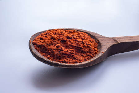 spicy ground red pepper in an old wooden spoon on a white background.