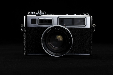 leatherette: Classic Rangefinder Film Camera on Black Surface Stock Photo