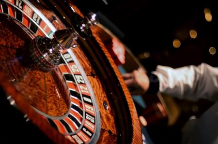 roulette: Rueda de ruleta del primer con el Croupier Ordenando Tokens en fondo desenfocado