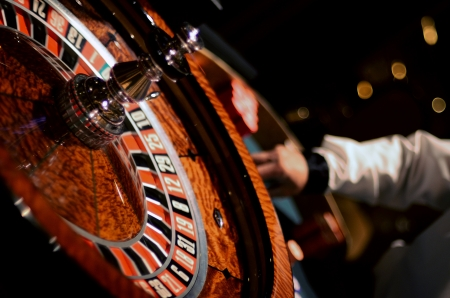 roulette: Ruota della roulette del primo piano con Croupier Ordinamento gettoni sfondo sfocato Archivio Fotografico
