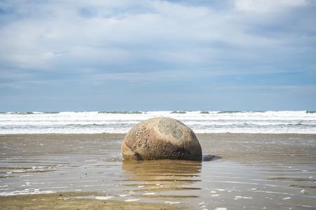 The Moeraki Boulders are lying along the Koekohe Beach on the Otago coast of New Zealand.