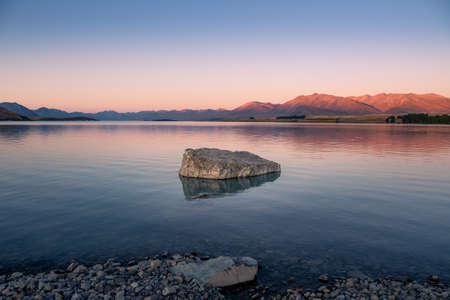 A lonely rock is standing in Lake Tekapo near the Church of the Good Shepherd with sunset in New Zealand.