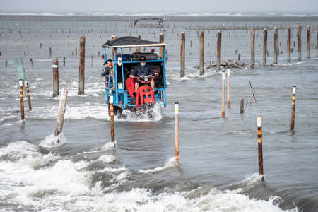Changhua, Taiwan - Feb 13, 2021:  The oyster truck full of tourists is crossing at high tide in Wang Gong Fishing Port.