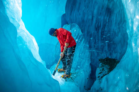 Canterbury, New Zealand - Dec 9, 2020: A tour leader is using the ice axe at the blue cave under Tasman Glacier in Mt Cook National Park.