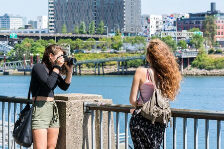 Female portrait photographer taking pictures of a female model along the river in a large city.
