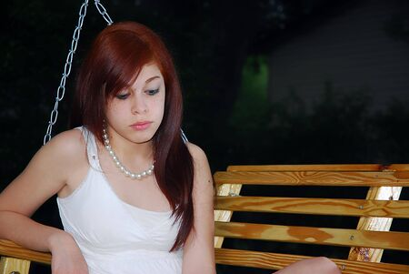 Beautiful little red head teen sitting on a swing