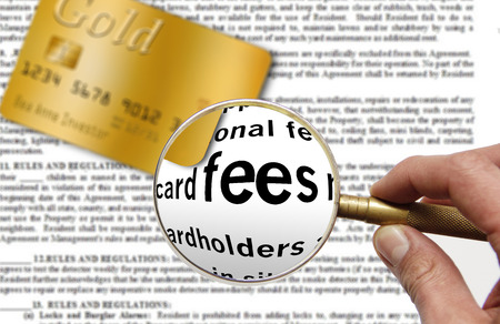 A magnifying glass in a hand hovers over the word fees in a credit card contract. A credit card is also in the picture.