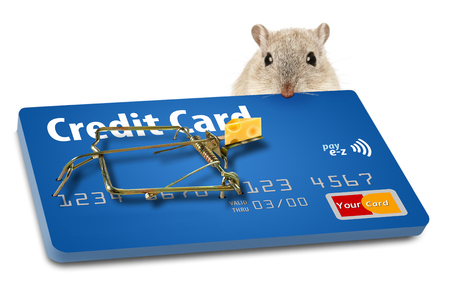 The concept of getting caught in a credit card trap when signing up for a new card is illustrated with a mousetrap baited with cheese. The mousetrap is a credit card with the trap hardware attached. This is an illustration. Stockfoto