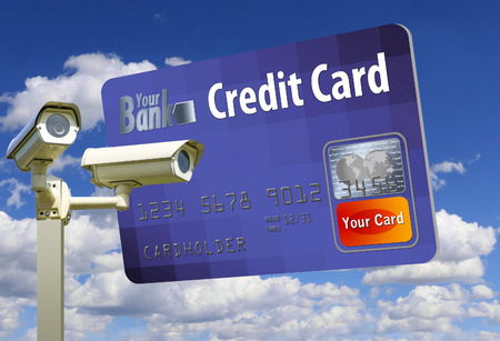 A generic, mock (safe to publish) credit card is seen next to a pair of security cameras to illustrate the idea of card and ID security.