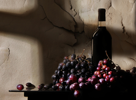 A bottle of wine with wine grapes is seen in front of aged and peeling paint in this sunlit photograph. Light is from a window.