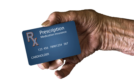 An elderly hand holds a  supplement prescription drug insurance ID card. This is a photograph. Фото со стока