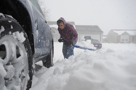 This is a current 2019 view a woman shoveling snow in her driveway in Franklin, Indiana, USA. This is a photo.