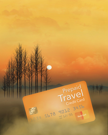 A prepaid travel credit card is seen in a meadow at sunrise with trees, fog, sky and clouds. This is an illustration