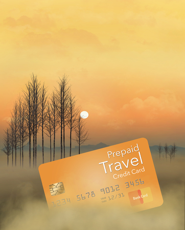 A prepaid travel credit card is seen in a meadow at sunrise with trees, fog, sky and clouds. This is an illustration Фото со стока - 117727267