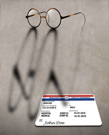 Old fashioned wire rim glasses cast a shadow across a table top and a U.S. Medicare Health Insurance card. Banque d'images - 132050606