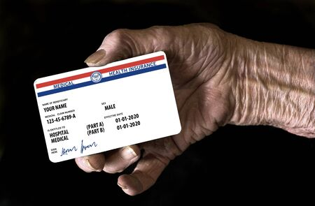 Here is a mock, generic, 2020 Medicare Health Insurance card held in an elderly hand. It does not use the word Medicare on the card but resembles a real Medicare card.  This is a photo illustration.