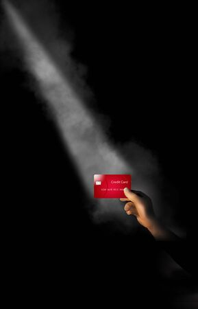 A hand holds a credit card in a shaft of light with a little fog. The theme is focusing on credit cards or one card in particular.