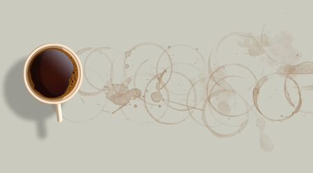 A cup of coffee is seen from above and also visible are rings of coffee stains extending across the page. Stockfoto