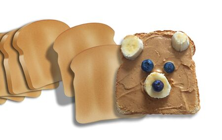 A piece of toast is decorated with peanut butter, banana slices and blue berries to create a cute bear cub face. The image is isolated on a white background.