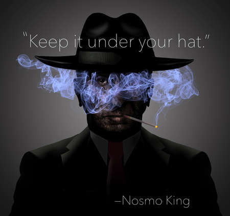 "This no smoking image shows a dark ominous man in shadows with light blue cigarette smoke over his face and trapped under the brim of his fedora. NosmoKing is his name. Letters of his name spell ""no smoking"""