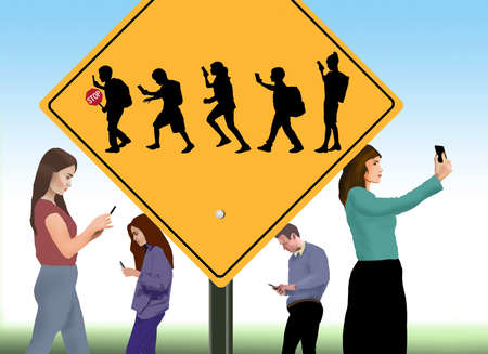 A school crossing sign includes silhouettes of children using cell phones. Фото со стока