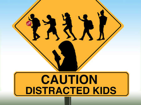 A school crossing sign includes silhouettes of children using cell phones. Stok Fotoğraf