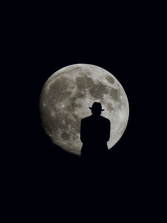 A man in a fedora stands on a hilltop watching a full moon at night. Фото со стока
