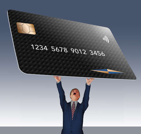 A man in a suit struggles to hold a hug credit card over his head in this 3-D illustration. Illustrates credit card debt.
