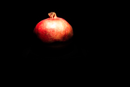 Red pomegranate in front of a dark background Stock Photo