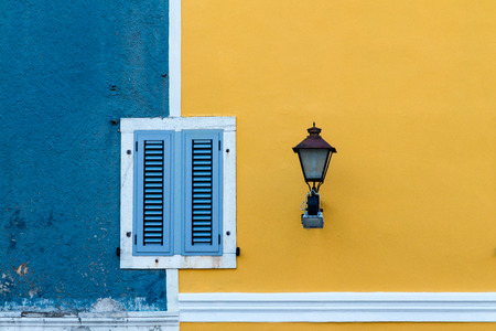 Facade in blue and yellow with windows and street light Stock Photo