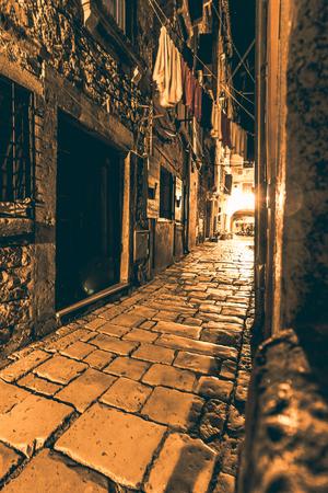 Small cobblestone alley in Rovinj at night Standard-Bild